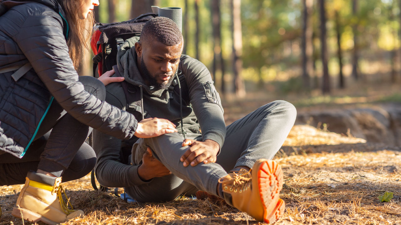 man and woman hiking and experiencing joint pain