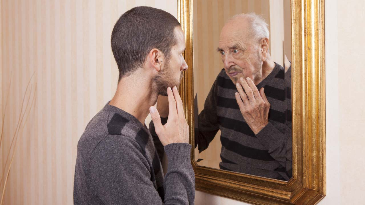 young man looking in mirror at older self with no testofen fenugreek or testosterone